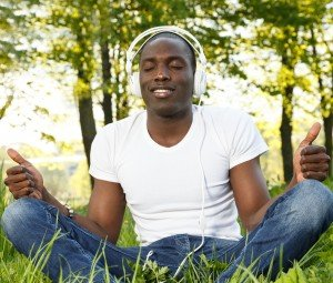 Positive young african american man in white shirt listens music in a park